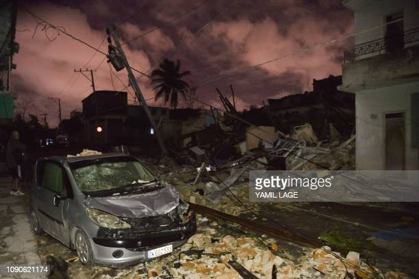 A damaged car is seen among building rubble in the tornadohit Luyano neighborhood in Havana early on January 28 2019 A rare and powerful tornado that...