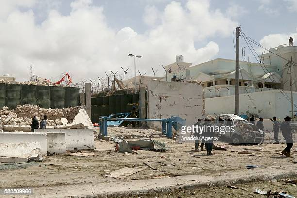 Damaged car is seen on the debris of buildings after a bomb attack with bomb-laden vehicles over the United Nations, African Union Mission in Somalia...