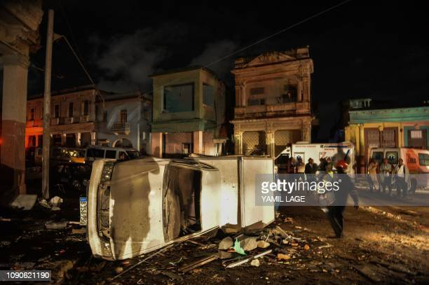A damaged car lies on its side in the tornadohit Luyano neighborhood in Havana early on January 28 2019 A rare and powerful tornado that struck...
