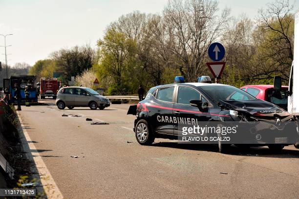 A damaged car of the Italian Carabinieri police is pictured next to the wreckage of a school bus that was transporting some 50 children on March 20...