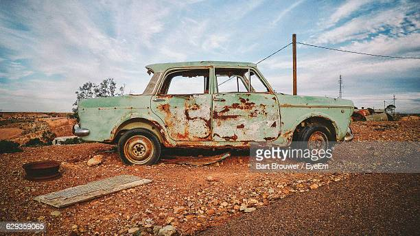 damaged car on field against sky - coober pedy foto e immagini stock