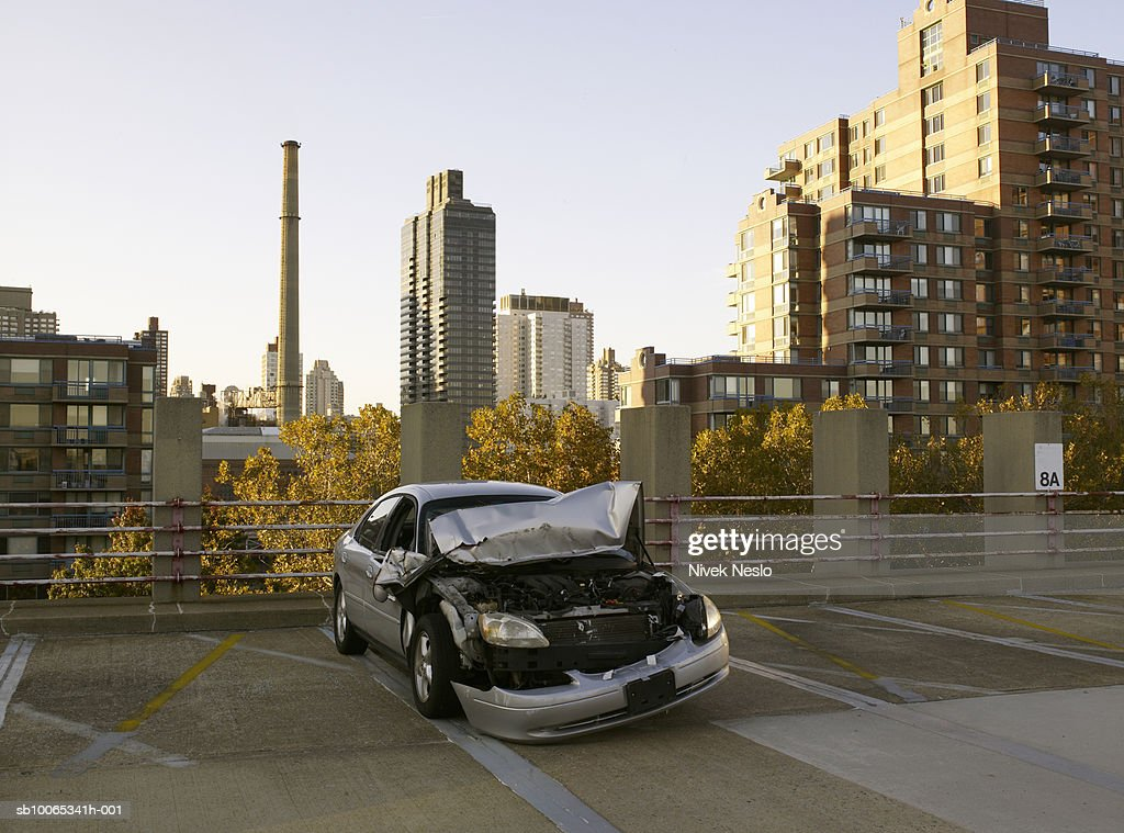 Damaged car on rooftop parking garage : Foto stock