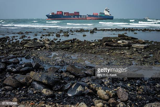 Damaged cargo ship lies near Taiwan's north coast on March 26, 2016 in Shihmen, Taiwan. An oil slick from a container ship which ran aground off...