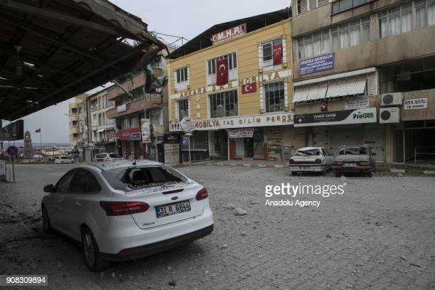 Damaged cars and buildings are seen after rockets fired from across the border landed in Turkeys Reyhanli district in southern Hatay province of...