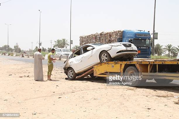 Damaged cars are pulled after a suicide bomber drove his explosiveladen vehicle into a crowded checkpoint at the eastern entrance of Khalis district...