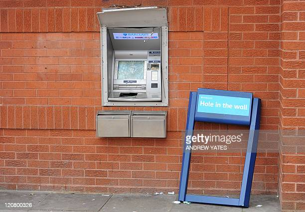 A damaged cash point machine is pictured at a Barclays Bank branch in Handsworth Birmingham central England on August 9 following a third night of...