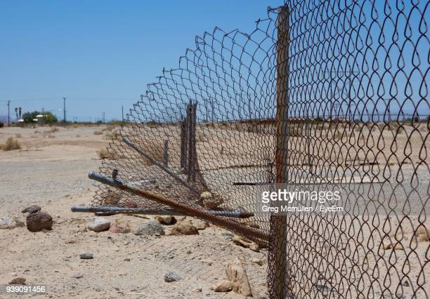 damaged chainlink fence on field against clear sky - chainlink fence stock pictures, royalty-free photos & images
