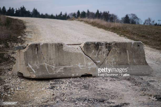 damaged concrete barricade on dirt road - barricade stock photos and pictures