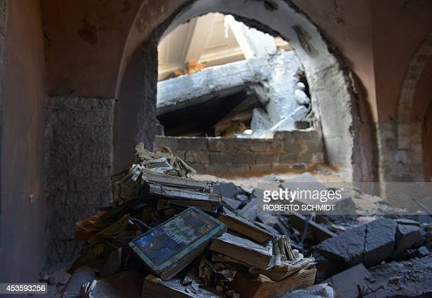 Damaged copies of Islam's holy book the Koran lie at the Omari mosque on August 12 2014 in Jabalia in the northern Gaza Strip after it was hit by an...