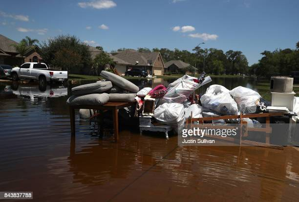 Damaged furniture and personal belongings sit in front of a flooded home on September 7 2017 in Richwood Texas Over a week after Hurricane Harvey hit...