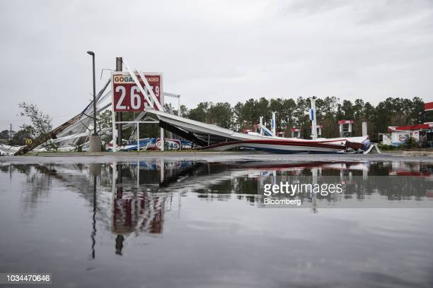 A damaged gas station is reflected in a puddle after Hurricane Florence hit in Wilmington North Carolina US on Saturday Sept 16 2018 In flooded...