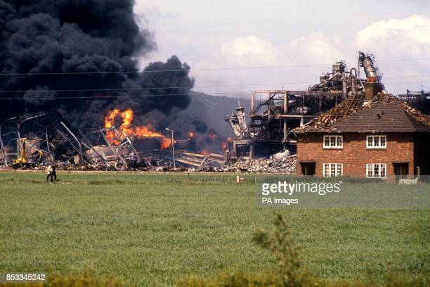 Damaged houses near the vast column of smoke and flame from the devastated factory at the Nypro UK chemical plant at Flixborough North Lincolnshire