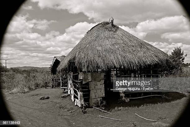 damaged hut on field against cloudy sky - hut stock pictures, royalty-free photos & images