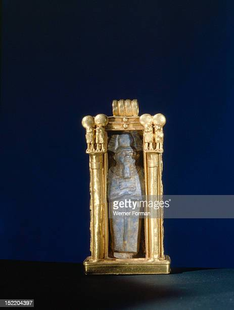 Damaged lapis lazuli amulet of the god Ptah re used within a gold shrine from the tomb of Wen Djeba En Djed senior official of Psusennes I Flanking...
