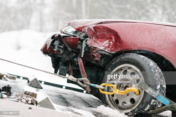 damaged maroon car on tow truck during winter - crash photos stock-fotos und bilder