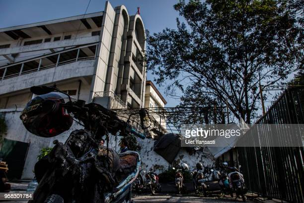 A damaged motorcycle is seen outside of Surabaya Centre Pentecostal Church as they clean the road following a blast at the church a day earlier on...