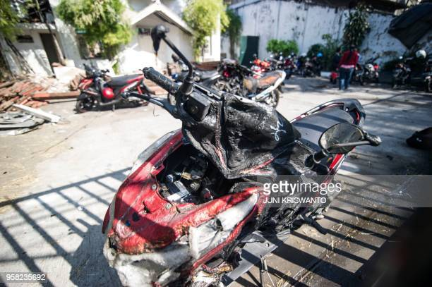 A damaged motorcycle is seen outside the Gereja Pantekosta Pusat Surabaya in Surabaya on May 14 following a blast outside the church a day earlier A...