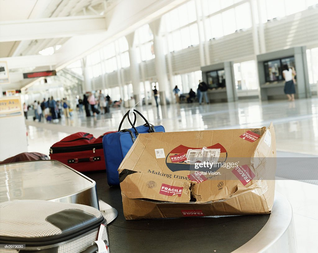 Damaged Package on a Airport Baggage Conveyor Belt : Stock Photo