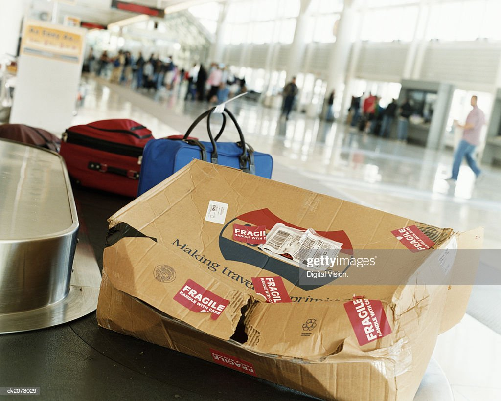 Damaged Package on an Airport Baggage Collection Conveyor Belt : Stock Photo