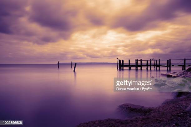 Damaged Pier In Sea Against Purple Sky At Sunset