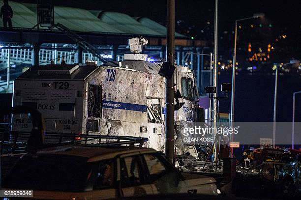 Damaged police vehicles and cars are pictured on December 10 2016 on the site where a car bomb exploded near the stadium of football club Besiktas in...