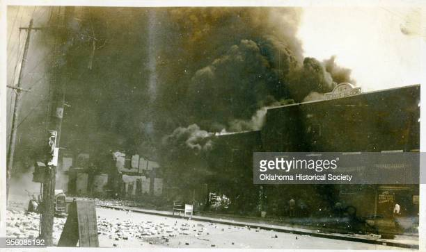 Damaged properties and smoke coming from buildings following the Tulsa Race Massacre, Tulsa, Oklahoma, June 1921.