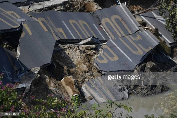 A damaged section of road is seen at an accident site after a road collapse in Foshan in China's southern Guangdong province on February 8 2018 Eight...
