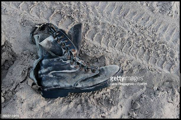damaged shoe on sand - leather boot stock pictures, royalty-free photos & images