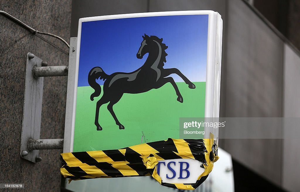 A damaged sign is seen covered in repair tape as it hangs outside a Lloyds TSB bank branch, part of the Lloyds Banking Group Plc, in London, U.K., on Monday, Oct. 15, 2012. U.S. homeowners filed a lawsuit against 12 banks, including Lloyds Banking Group Plc, Barclays Bank Plc, and JPMorgan Chase & Co., claiming that manipulation of the benchmark Libor lending rate made their mortgage repayments more expensive. Photographer: Simon Dawson/Bloomberg via Getty Images
