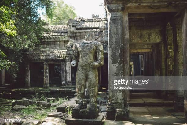damaged statue at historic temple - bortes stock-fotos und bilder