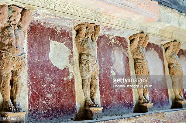 damaged statues on old ruin wall at pompeii - pompeii stock photos and pictures