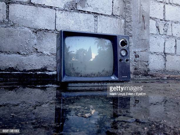 Damaged Television Set On Footpath Against Wall