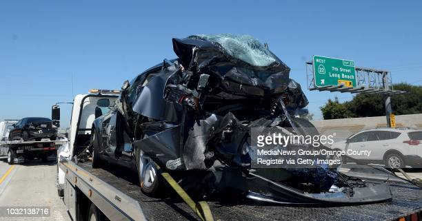 A damaged Tesla right and Honda Civic sit on tow trucks after a collision in the HOV lane on the northbound 405/22 Freeway in Seal Beach after a...