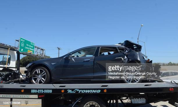 A damaged Tesla sits on a tow truck after a collision in the HOV lane on the northbound 405/22 Freeway in Seal Beach after a fatal traffic accident...