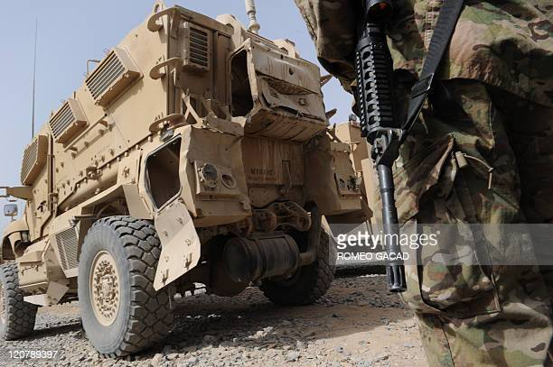 A damaged US Mine Resistant Ambush Protected armored vehicle awaits repair at the maintenance yard at the Forward Operating Base HowzeMadad in...
