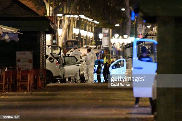 A damaged van believed to be the one used in the attack is surrounded by forensics officers in the Las Ramblas area on August 17 2017 in Barcelona...
