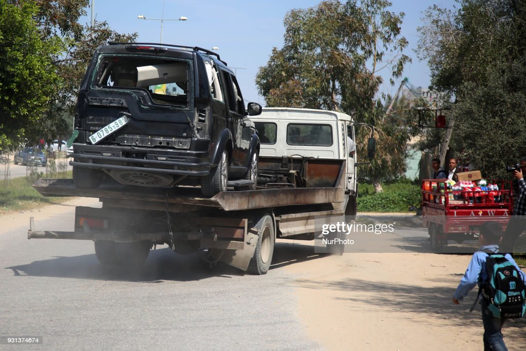 A damaged vehicle is removed from the site of an explosion that occurred as the convoy of Palestinian Prime Minister Rami Hamdallah entered Gaza through the Erez crossing with Israel, on the main road in Beit Hanoun, Gaza Strip, Tuesday, March 13, 2018.The Fatah party of the prime minister called the explosion an assassination attempt and blamed Gaza militants. Hamdallah was unharmed and went on to inaugurate a long-awaited sewage plant project in the northern part of the strip