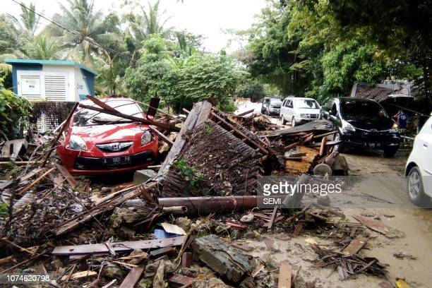A damaged vehicle is seen amid wreckage from buildings along Carita beach on December 23 after the area was hit by a tsunami on December 22 following...