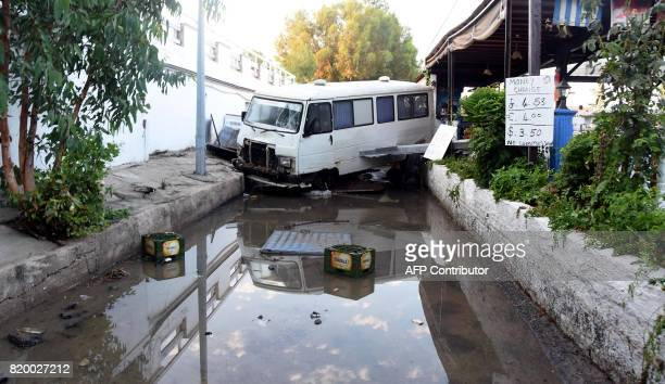 TOPSHOT A damaged vehicle is seen following a sea surge caused by an earthquake on July 21 2017 in Bodrum southwestern Turkey Two foreigners died and...
