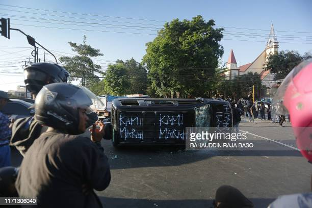 Damaged vehicle sits on its side after it was overturned by a group of protesters in front of the Hasanuddin University campus in Makassar, Sulawesi...