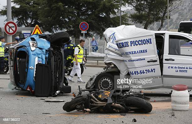 Damaged vehicles and a motorcycle are pictured at the site of an accident near the toll station at the A8 motorway on September 17 2015 in La Turbie...