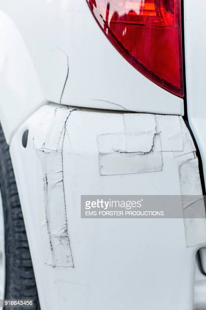 damaged white car with duct tape outdoors