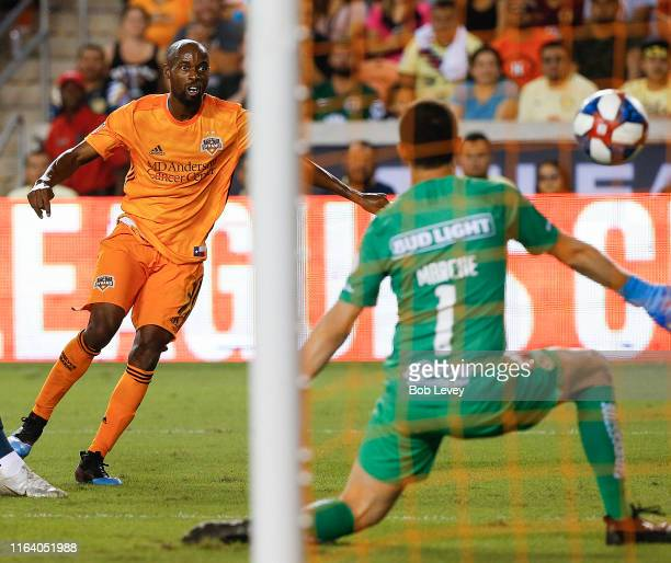 DaMarcus Beasley of Houston Dynamo scores the equalizer in the second half as he shoots past Agustin Marchesin of Club America during a quarterfinal...