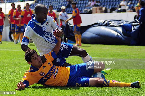 Damarcus Beasley of Puebla struggles for the ball with Israel Jimenez of Tigres during a match as part of the Apertura 2011 at Cuauhtemoc Stadium on...