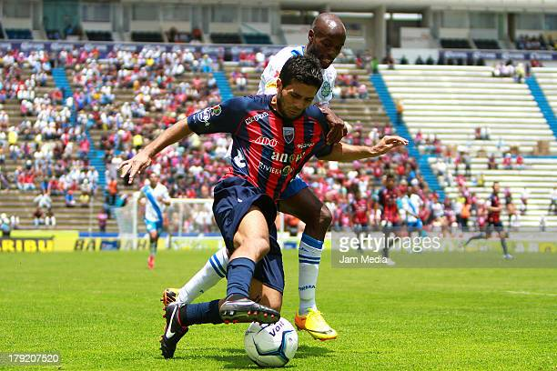 Damarcus Beasley of Puebla struggles for the ball with Walter Erviti of Atlante during a match between Puebla and Atlas as part of the Apertura 2013...