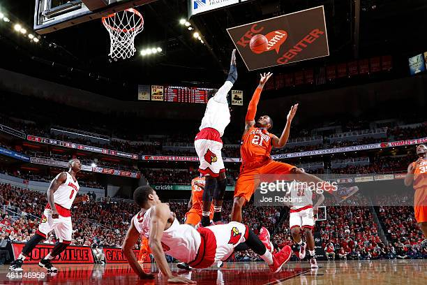 Damarcus Harrison of the Clemson Tigers drives to the basket against Mangok Mathiang and Wayne Blackshear of the Louisville Cardinals in the first...