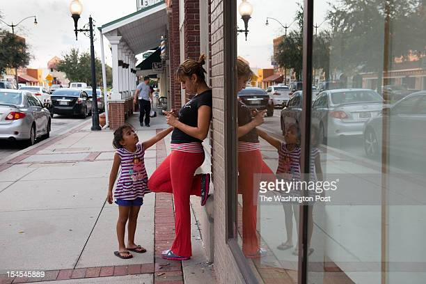 Damaris Pagan of Puerto Rico, and her daughter, Yahaira Colon stand on the main street in historic Kissimmee Florida. She says she is definitely...