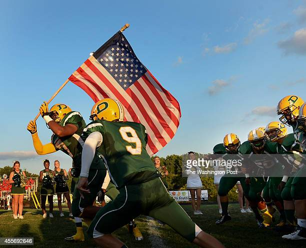 Damascus High School senior Stephon Jacob carries an American flag as he leads his teammates onto the field for the start of the game between the...