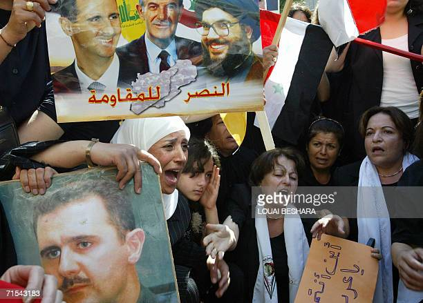 Syrian women hold a banner bearing portraits of Syrian Presidents Hafez and Bashar alAssad and Hezbollah leader Hassan Nasrallah reading in Arabic...