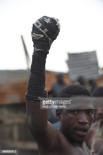 A dambe boxer raises fist wrapped with cloth and knotted with a cord preparing to fight during a dambe match at KaraIsheri in Ogun State southwest...